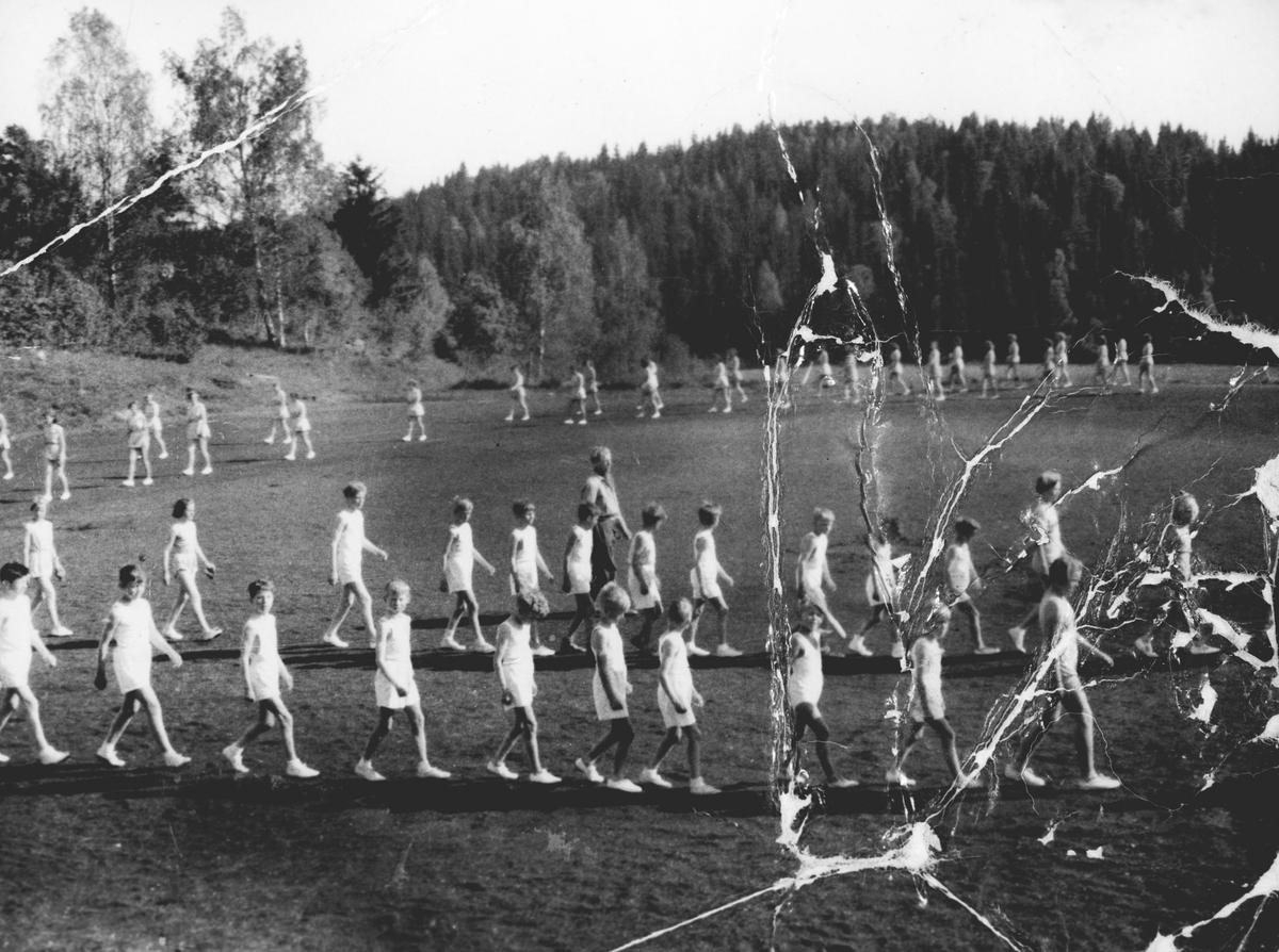 Første guttetroppen i Oppegård Idrettslag. Hvitkledde gutter, marsjerende på idrettsplass.