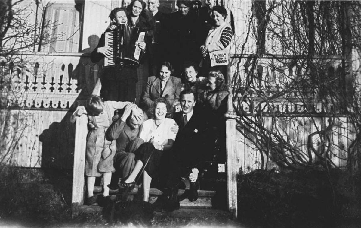 Familiefest samlet på trappen med trekkspill