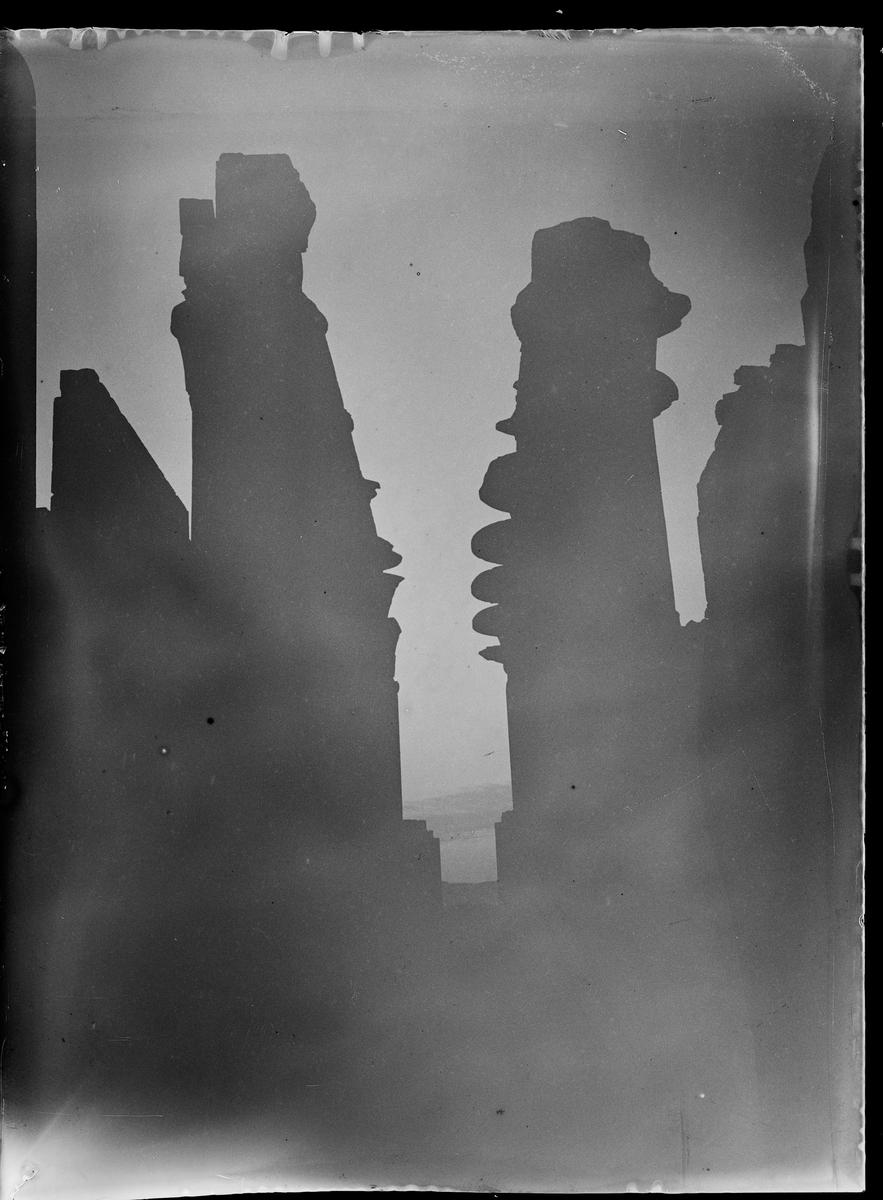 Mørkt bilde av tårn med vann i bakgrunn.