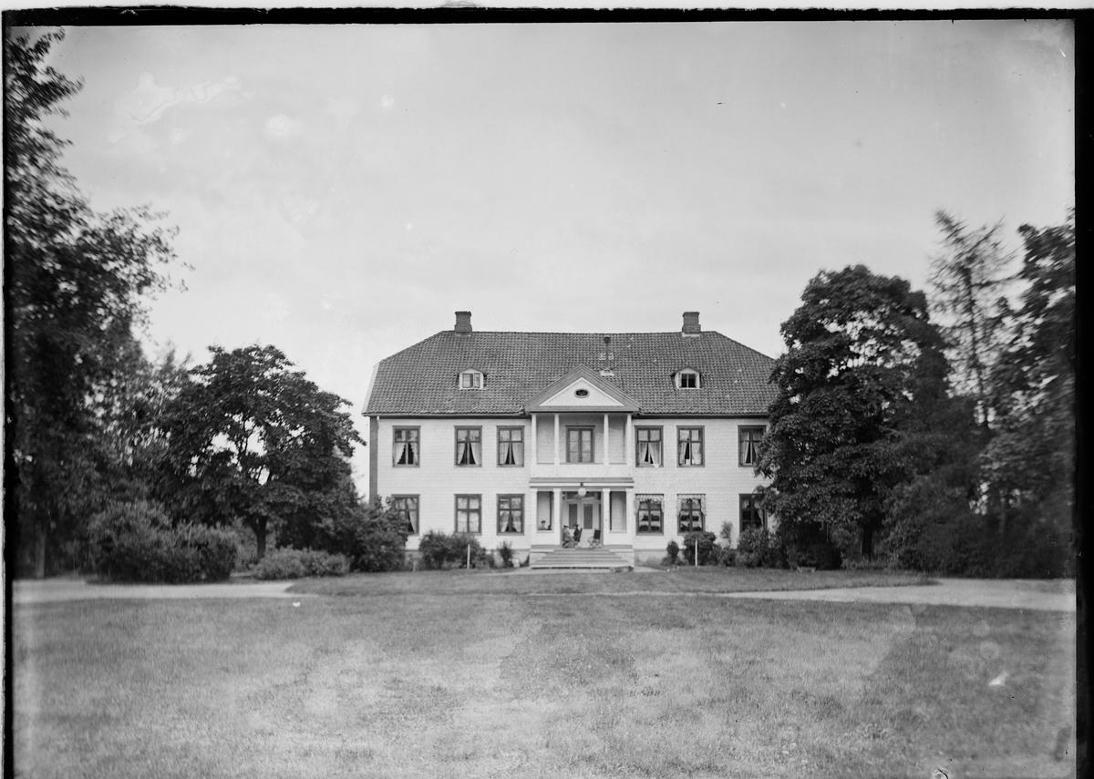 Det gamle hovedhuset på Eidsvoll verk med hage og trær rundt.