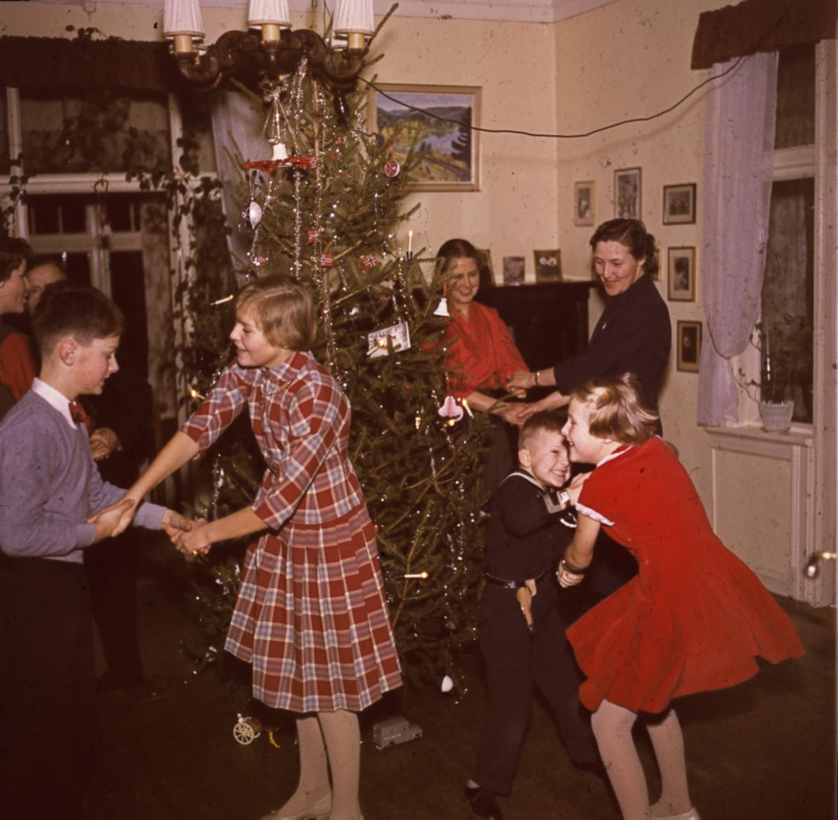 Foto av en famile som går rundt juletreet.