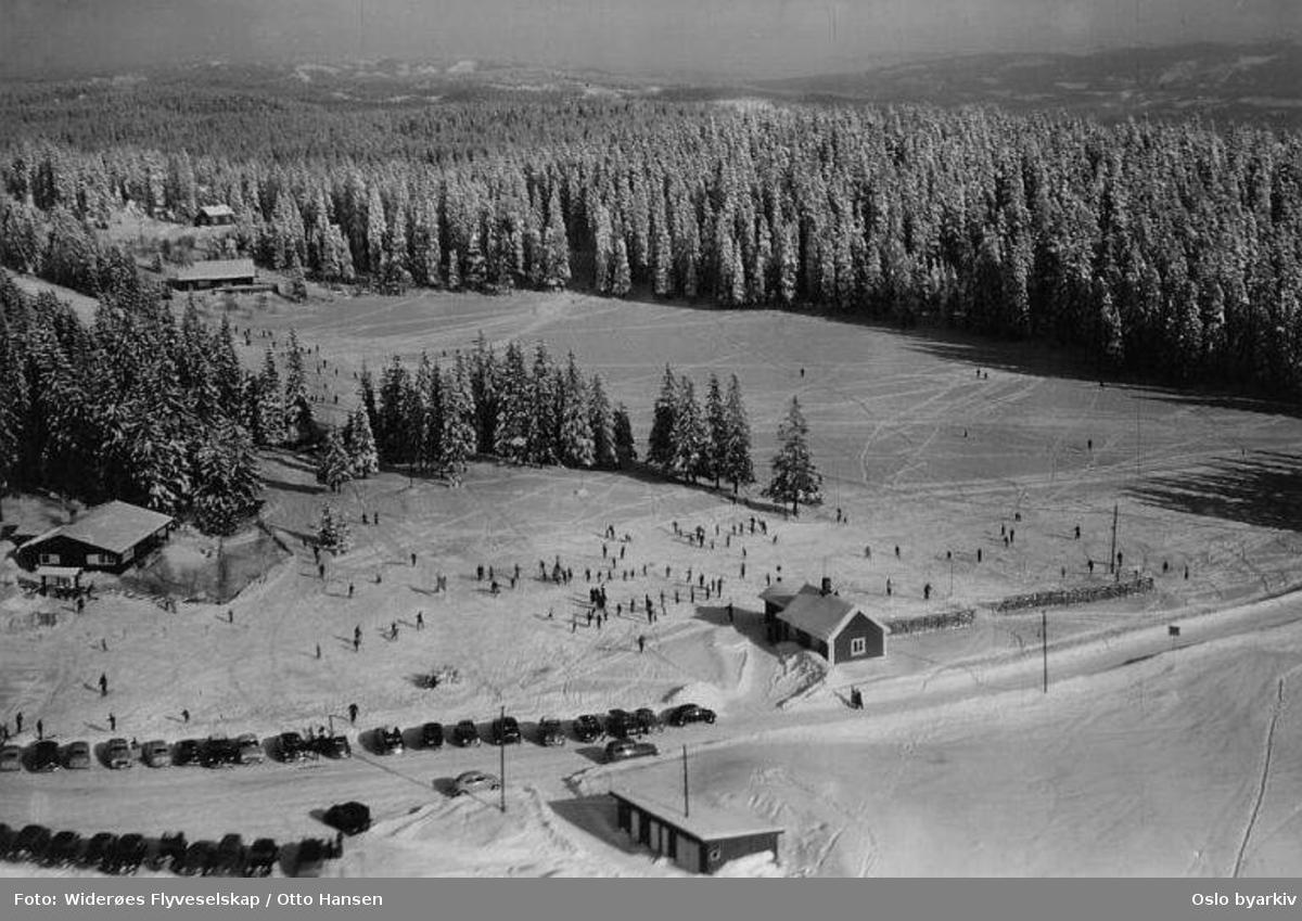 Øvreseterveien. Øvresetertjern. Tommkleiva. Tomm Murstad skiskole og barnehage (Tommleplassen). Hytte leid av Oslo skikrets. (Vinter) (Flyfoto)