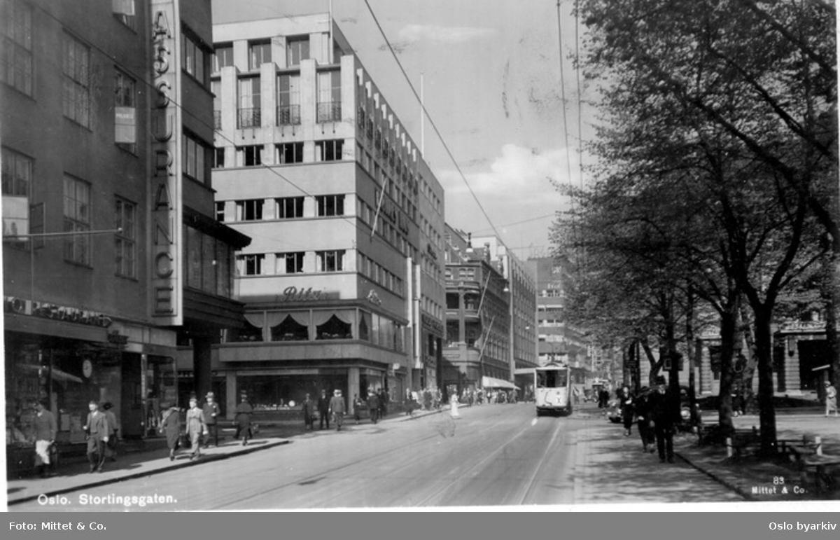 Stortingsgata ved Høyres Hus, hjørnet mot Universitetsgata (nåværende Roald Amundsens gate). Ritz restaurant. Hotel Continental bak. Butikker. Trikk, spaserende. Postkort 83.
