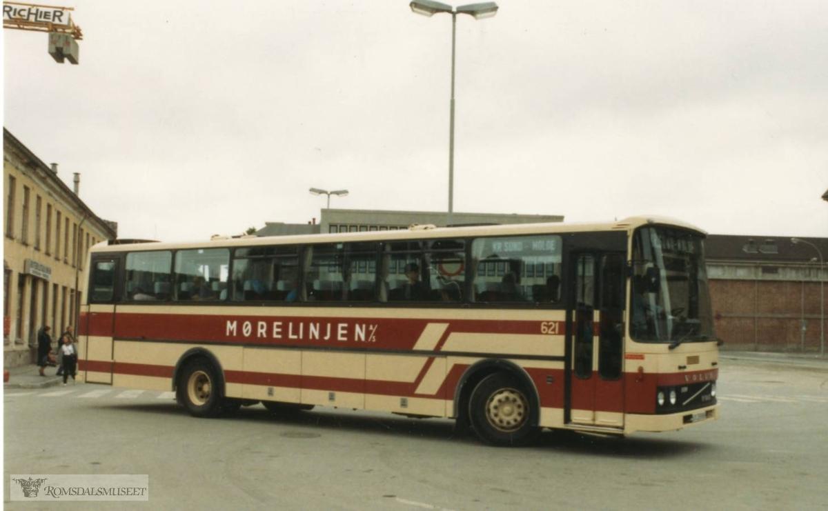 Mørelinjen A/S..Bussen var registret UX28986. Den var en av to like busser Mørelinjen A/S i Surnadal fikk i juni 1982. Den andre var UX28940. Merket var Volvo B10M og karosseriet ble bygd hos Vestfold Bil og Karosseri, med betegnelse VBK M600H-Ekspress. Dette var busser med høy standard beregnet for langrutene Trondheim-Molde/Kristiansund. De ble også brukt til turkjøring. .På bildet legger bussen i vei fra den gamle rutebilstasjonen på Leüthenhaven i Trondheim..I 1988 ble Mørelinjen fusjonert med Trollheimen Trafikk, Sunndalsøra. Bussene ble omlakkert og fikk fargene blå, brun og sølvgrå. Bussen ble etter hvert brukt mer på lokalruter og skoleruter, og den var i trafikk helt til 2006. Den ble så eksportert til Vilnius i Litauen. Der gikk den i flere år videre, i fargene den hadde etter 1988, og merket «Nettbuss Møre», som drev rutene på Nordmøre da den ble solgt..(fra Oddbjørn Skjørsæter sine samlinger i Romsdalsarkivet)
