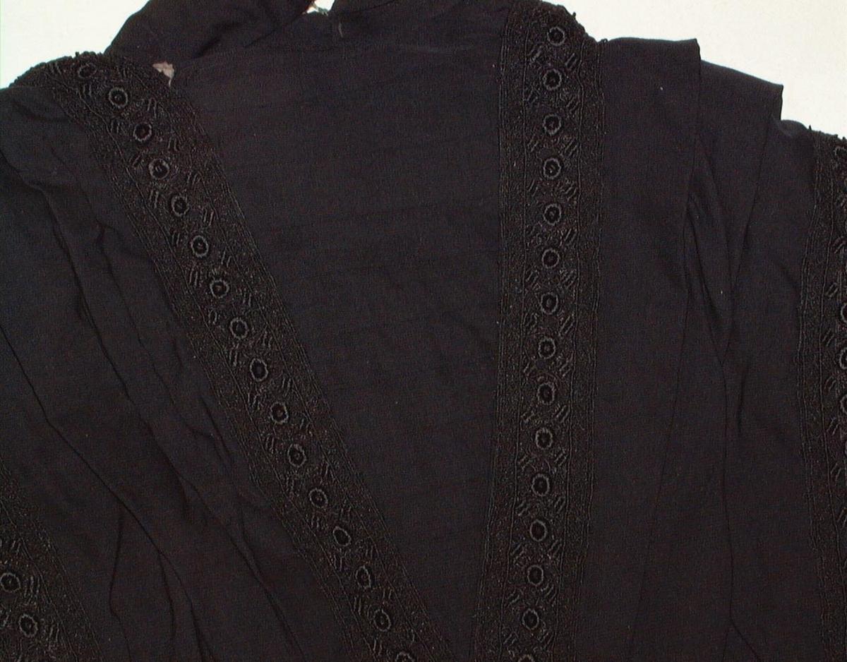 GM24795 B og C spiler 16 og 17 cm lange hekter/maljer og spiler fjernet p. g. a. rust utfyllende beskrivelse i kort kartoteket.  Kypertvevet. 1 bakstykke, 2forstykker. Åpning midt foran. Foret med hvit lerretsvevet bomull. V-formet bryststykke sydd på forets høyre side lukkeanordning på venstre. Oppstående krave, sydd på bryststykket, åpning bak. Utfyllende beskrivelse i kortkartoteket.