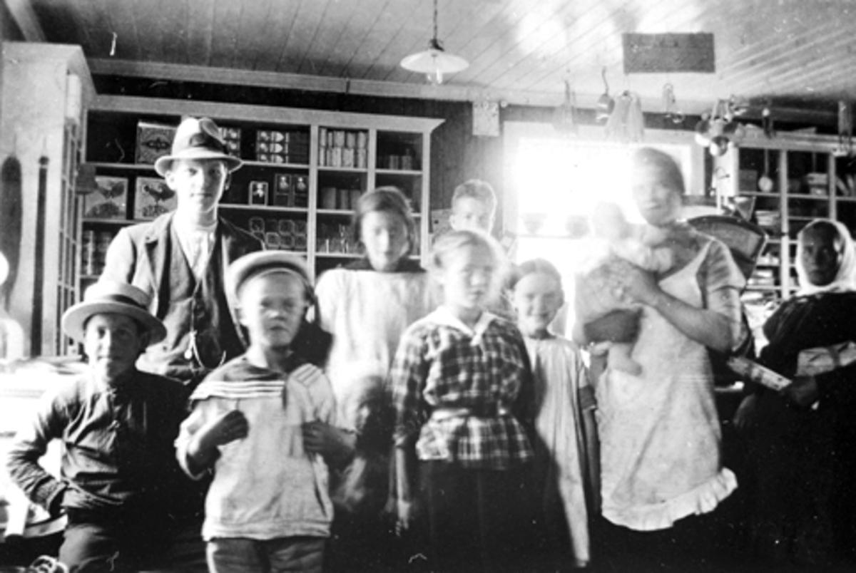 Interiør, Rud Samvirkelag, Rudshøgda, Ringsaker. Gruppe personer. Til venstre med hatt er bestyrer Asbjørn Berg.