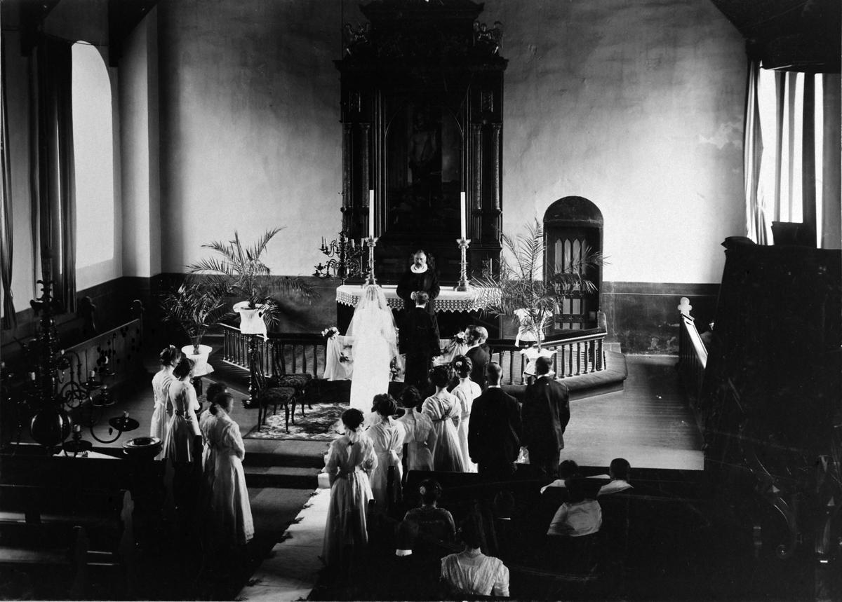 Bryllup i Furnes kirke, Ringsaker ca. 1905-1910. Brudepar foran alteret med prest, forlovere og ni brudepiker.
