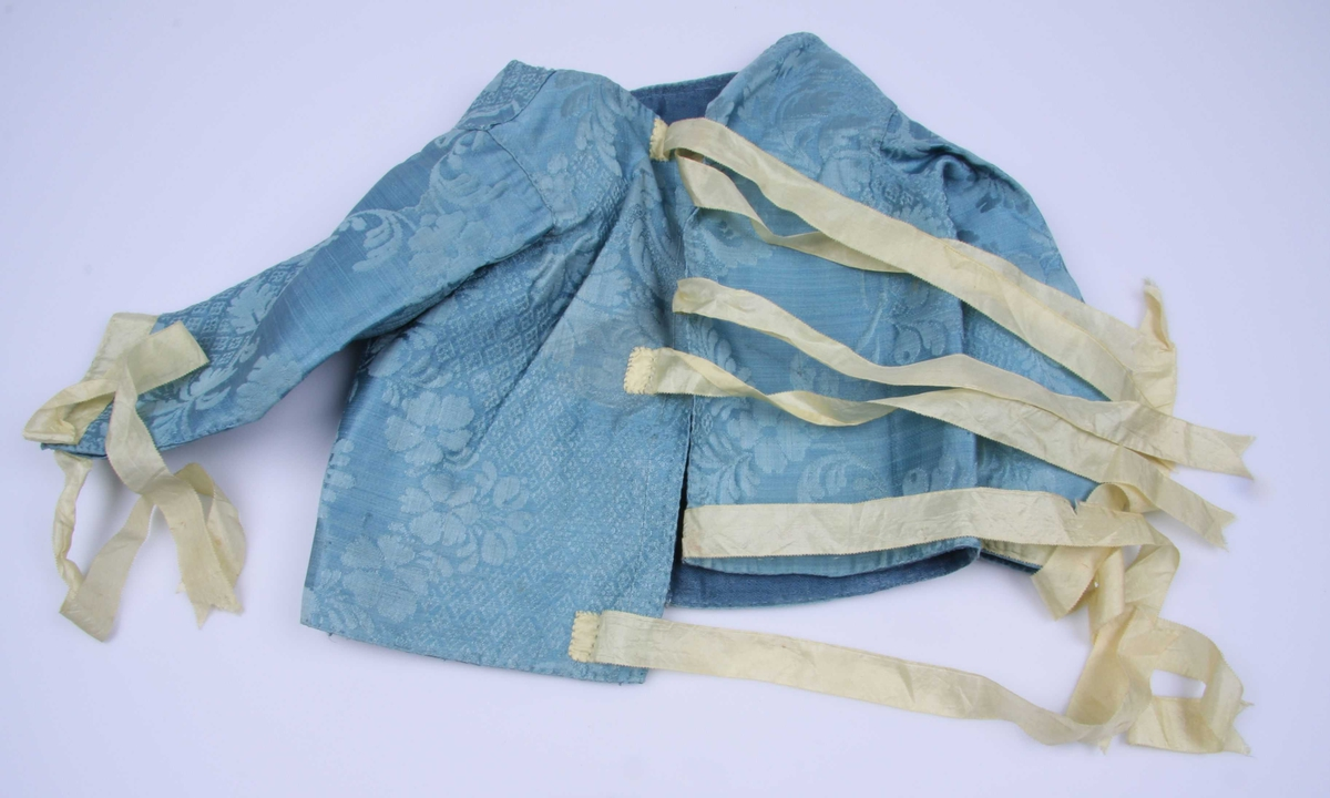 Av blå silkedamask med blomster og rutemønster. Splitt nederst på ermene som knytes sammen med gule silkebånd som også kanter ermet. Samme bånd til å knyte bak. Blått, vokset linfôr.