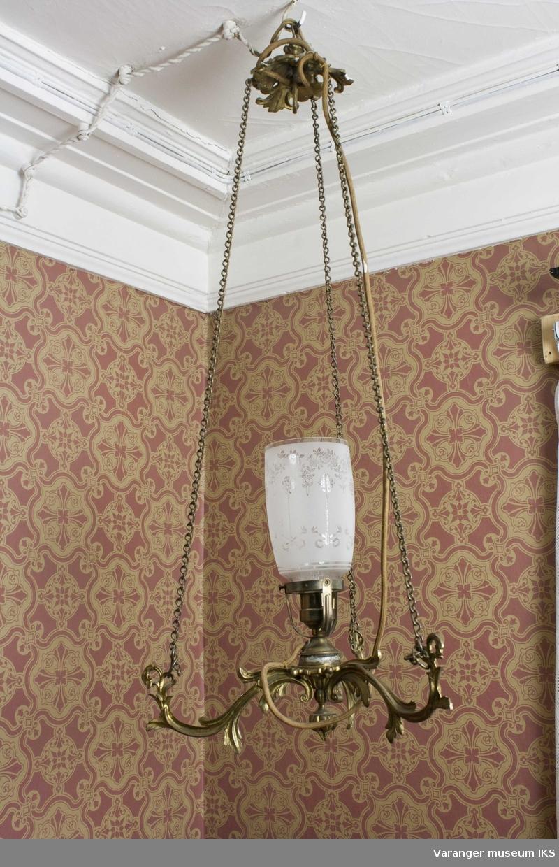 Elektrisk lampe i messing med tre armer. Kjetting oppheng med dekorert glasskuppel i midten.