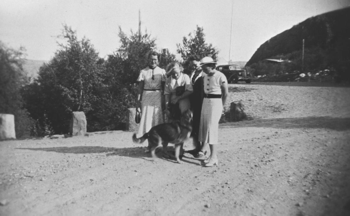 Fire damer i fine kjoler og hund.