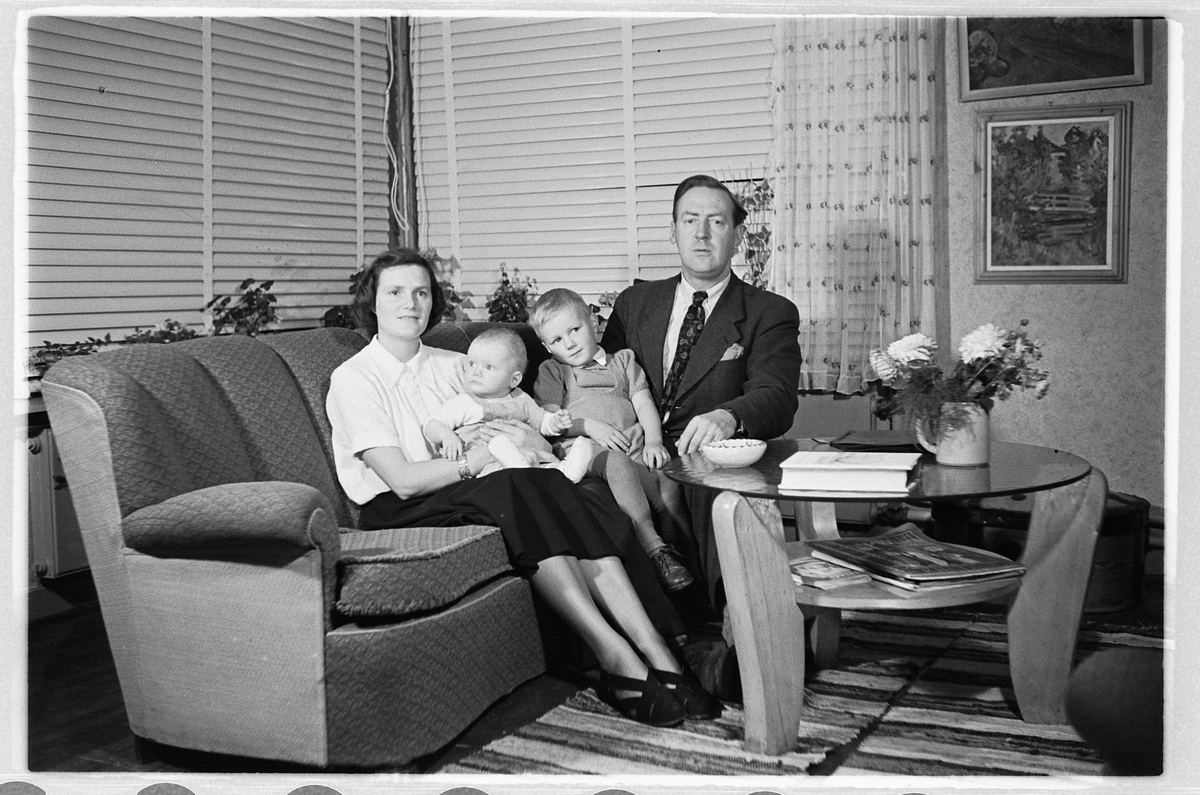 Interiør, stue. Kvinne og mann i en sofa med en baby og en gutt.