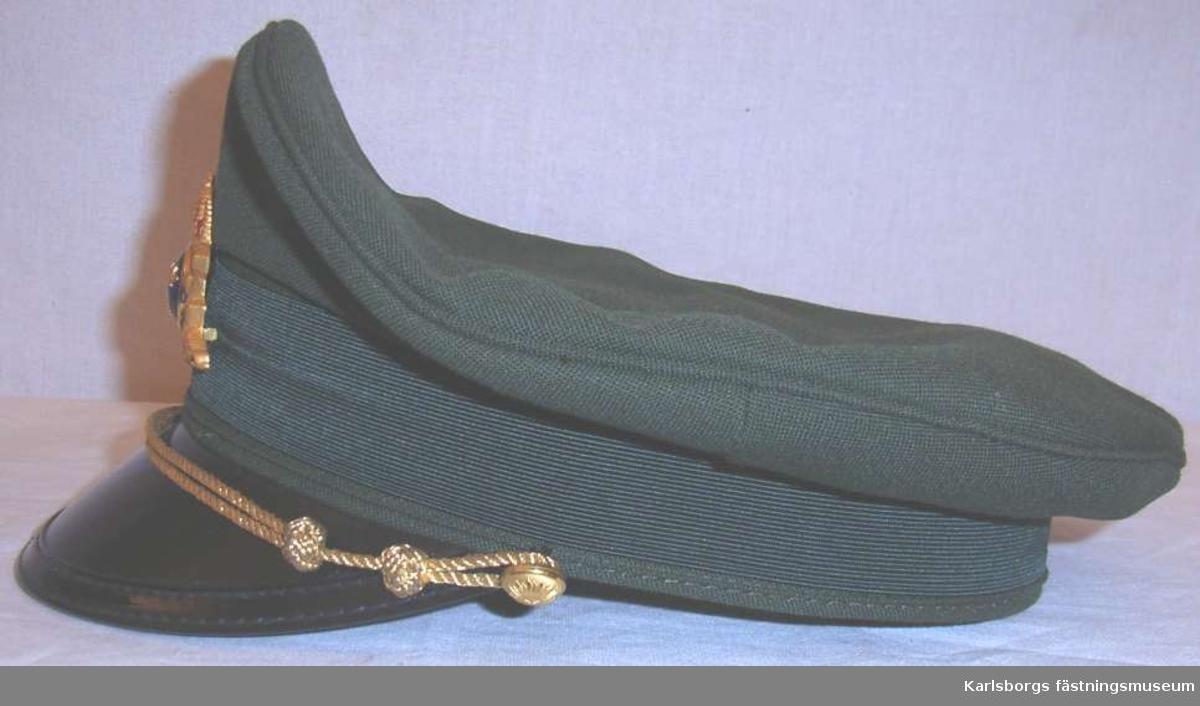 Storlek: 57 Grön skärmmössa av olivgröntt tyg med mösskärm av svart lackerat material Skärmens undersida är grön. Mössmärke mitt fram i guldmetall med blå knapp, tre kronor omringad av halmkrans och två korsade svärd. 2 mössremmar av guldtråd fästade vid liten guldknapp. Brun svettrem och helfodrad med grönt tyg invändigt. Mössans ståndare och stomme är i plast.
