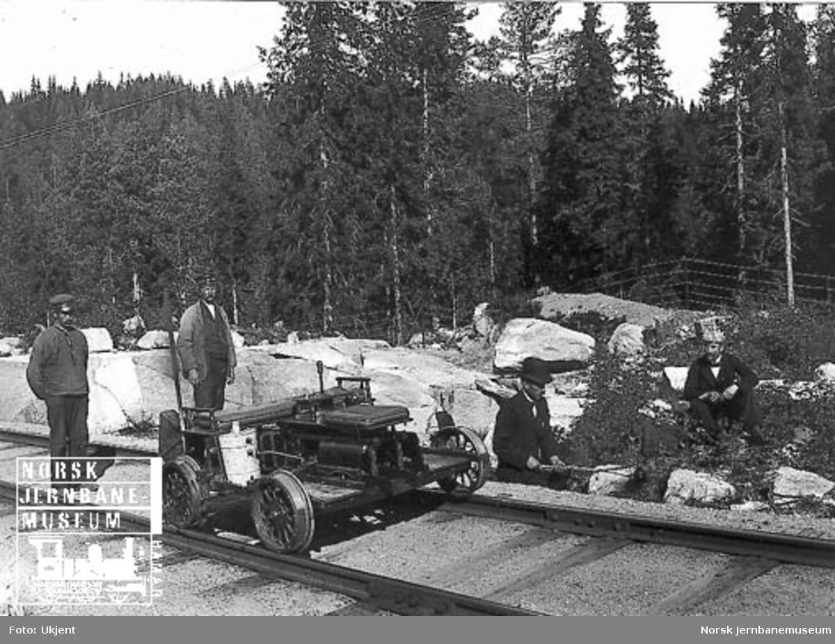 Fire menn, hvorav to banearbeidere, med firehjuls motortralle, på Gjøvikbanen