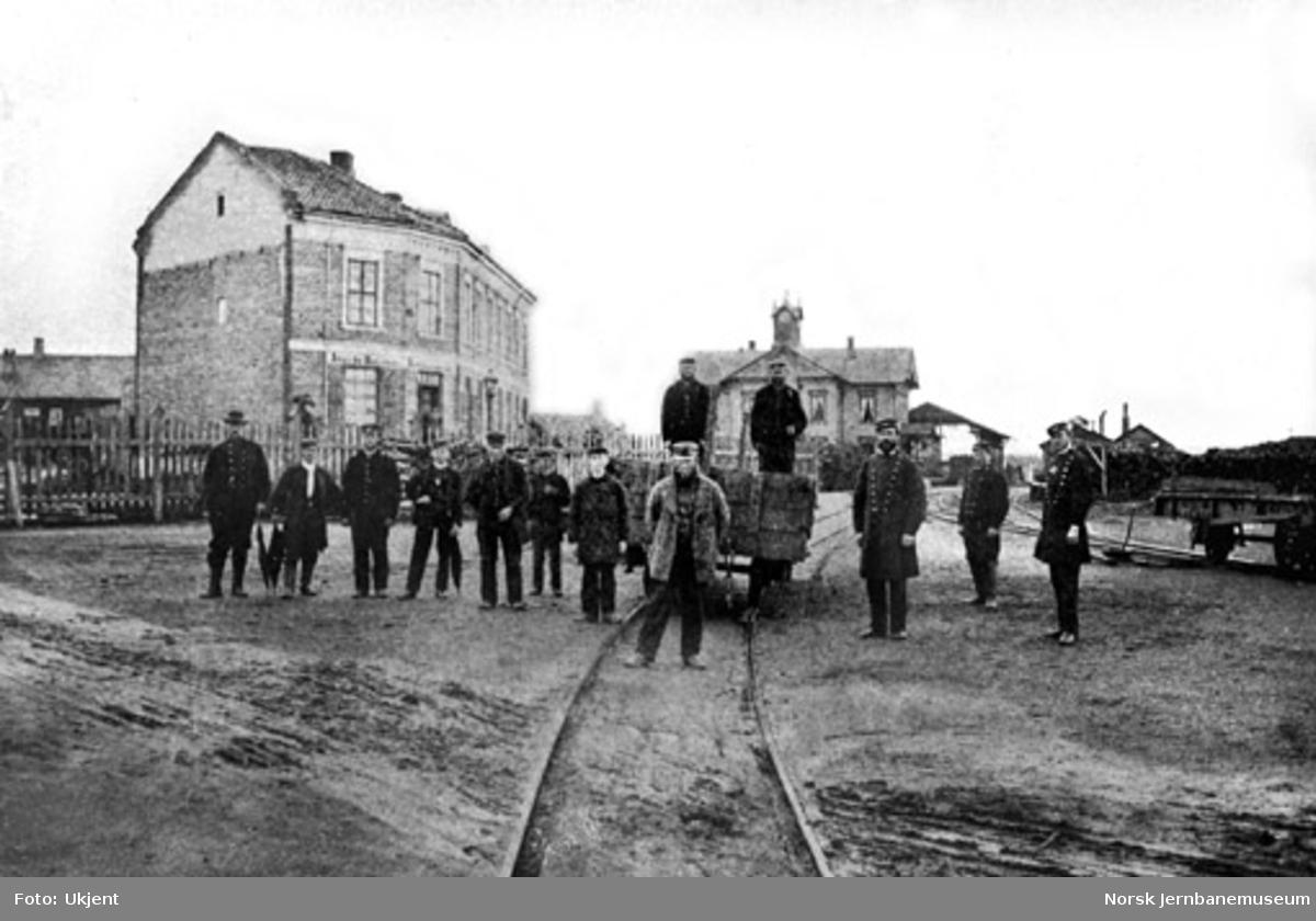 Personalet på Hamar stasjon oppstilt foran en vogn på bryggesporet med stasjonsbygningen i bakgrunnen