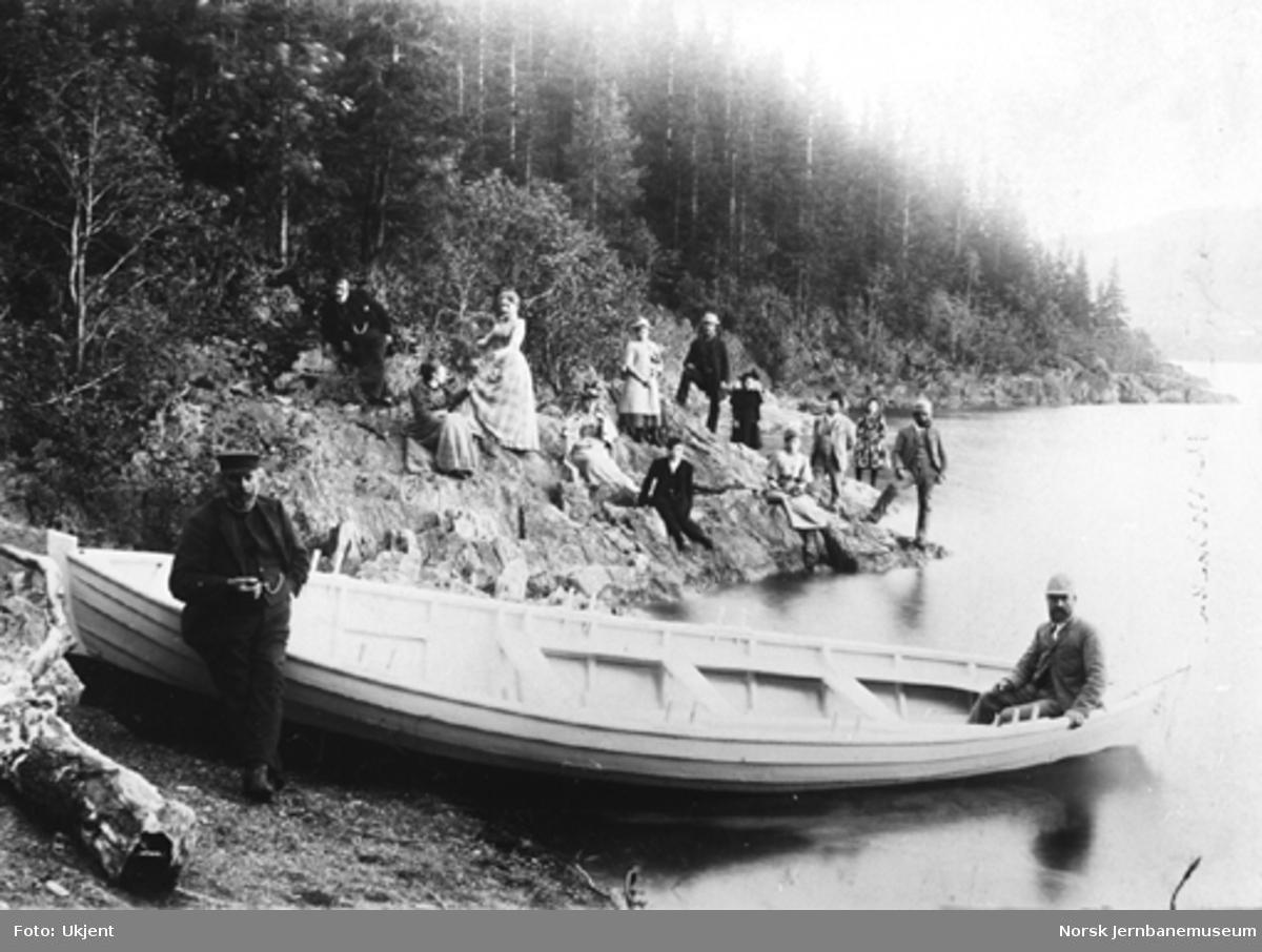 14 personer på utflukt på Helgeberget; robåt i forgrunnen