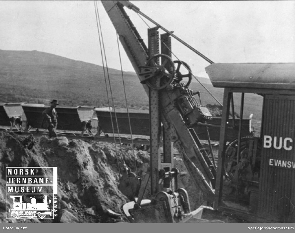 Bucyrus-gravemaskin med anleggsvagger i bakgrunnen, trolig på Dovrefjell
