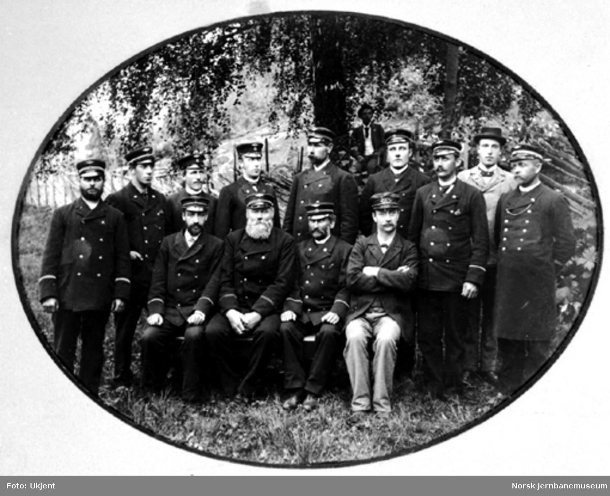 Gruppebilde tatt i landlige omgivelser av 12 jernbanefolk samt to i sivil, sannsynligvig på Hamar ca. 1895