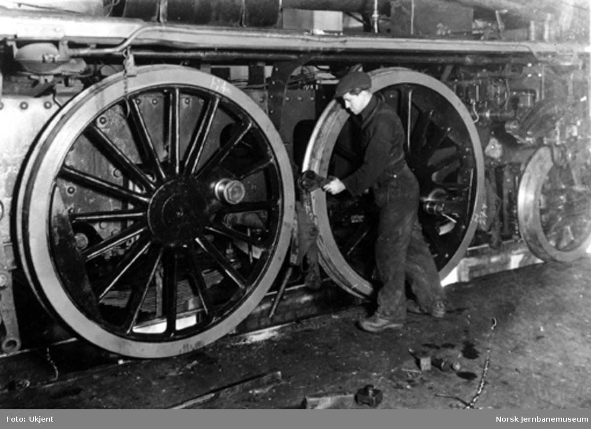 En verkstedarbeider monterer bremseklosser ved hovedrevisjon av damplokomotiv, trolig på Thunes mekaniske værksted