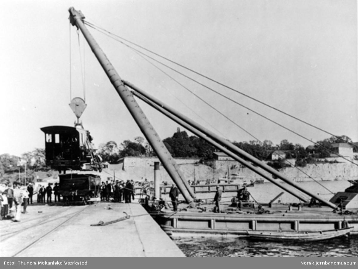 Smalsporet damplokomotiv type XXIII løftes i flytekran for transport fra Rådhusplassen til Østbanen