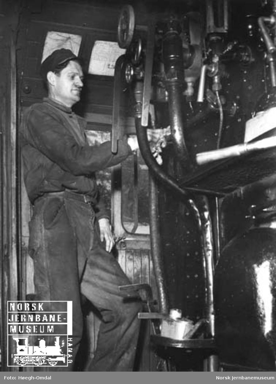 I full puss : Lokomotivpusser O. Aardal i gang med pussen i førerhytta på et damplokomotiv, trolig type 33a