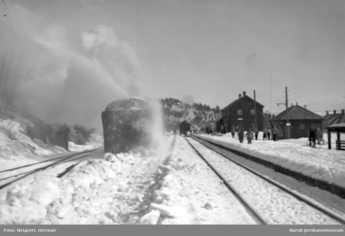Roterende snøplog i aksjon på Geilo stasjon, damptog kjører inn i spor 1