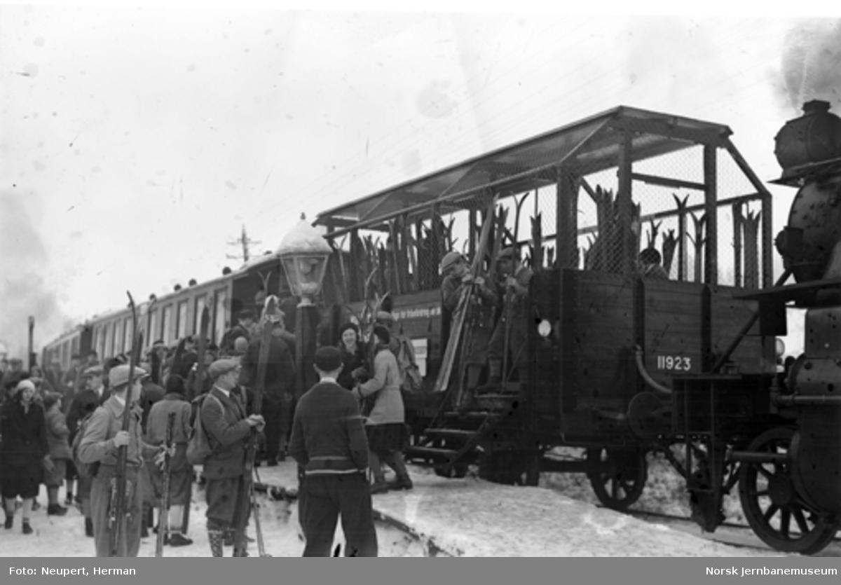 Persontog og skiturister på ukjent stasjon, forende av tanklok type 34 i bildekanten