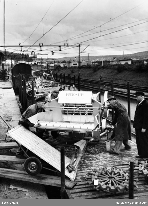 Opplasting av landbruksmaskiner på godsvogn på Grorud stasjon