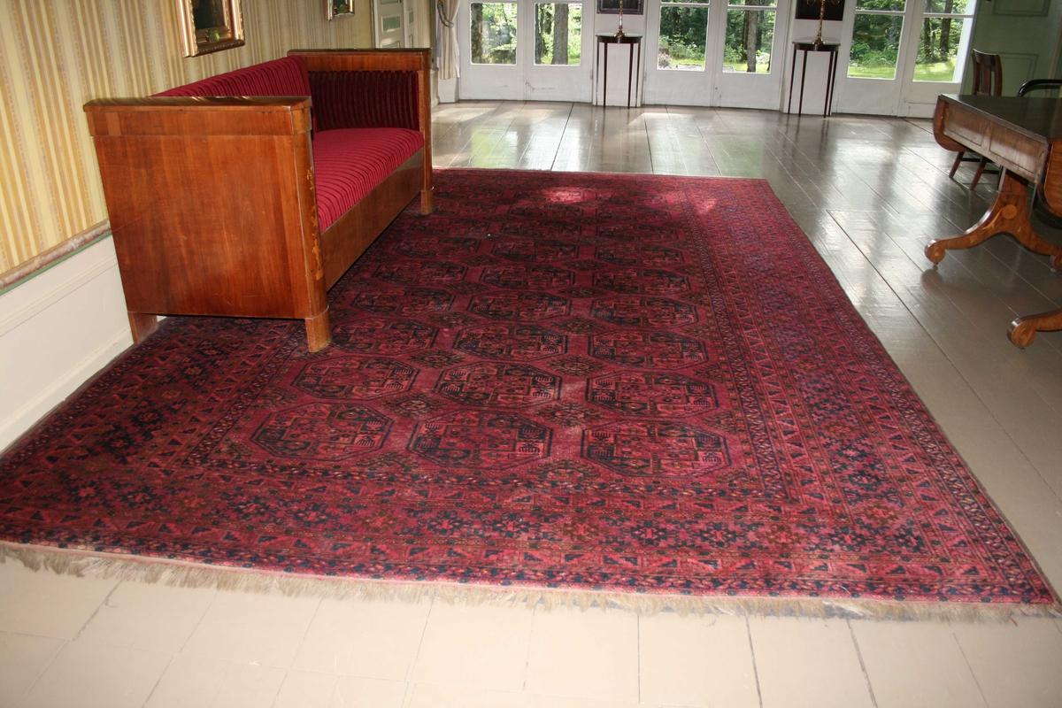 Afghansk gulvteppe. Dyp rødt med mønster: Elefantføtter og lysestake.  Bokharateppe