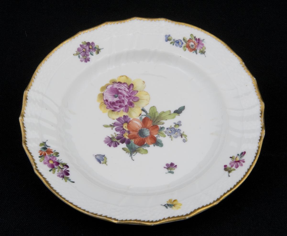 Salattallerken i porselen med håndmalt blomsterdekor, gullkant og riflet i godset.