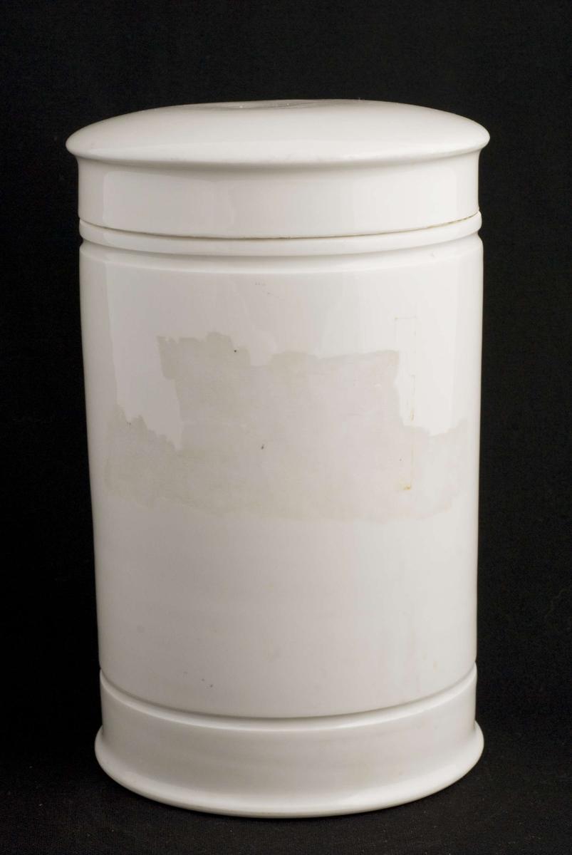 Standglass med overfallende lokk. Krukken er hviglasert innvendig og utvendig.Horisontale riller øverst og nederst. Plass til påmalt skrift (mangler).