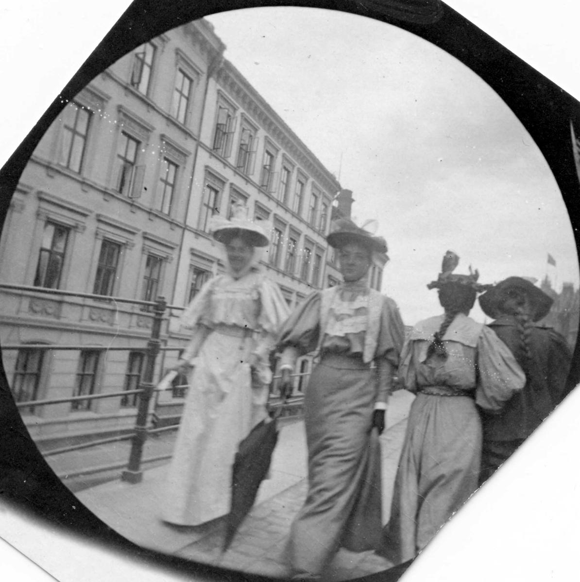 Frk.Bjelke og frk. Hvoslef spaserer langs gjerde i bygate, Oslo. To damer med ryggen til og bygårder.